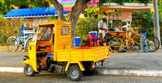 A tuk-tuk parked in front of two snack vendors with their trikes.
