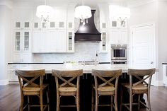 This kitchen is the perfect mix of rustic design elements with high glamour.  The black range hood makes such a statement against the all white cabinetry and the crystal chandeliers pendant chandeliers are a great counter point to the rustic x-back barstools.