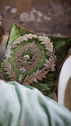 Opulently embroidered raised laurel wreaths surround the finely worked central motif in subtly aged gold and silver thread.