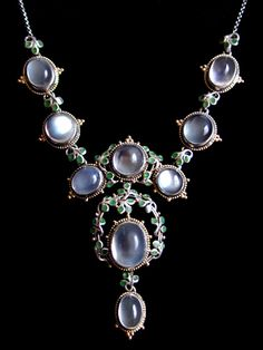 Liberty & Co. - JESSIE M. KING (1875-1949) LIBERTY & Co. A silver and gold necklace set with moonstones within borders of blue/green enamelled leaves surrounded by gold wire wirework and gold florets. The silver chain with a gold clasp. British. Circa 1900.