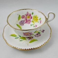 Beautiful tea cup and saucer made by Royal Standard. Tea cup and saucer have hand painted bouquets of flowers. Pattern is called Lorraine. Gold trimming on cup and saucer edges. Excellent condition (see photos). Markings read: Lorraine Royal Standard Fine Bone China England Please