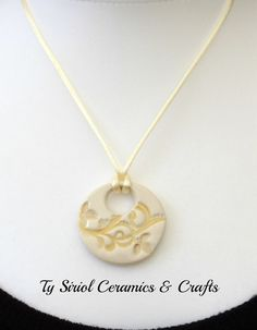 White and gold circular pendant on a cream by TySiriolCeramics, £18.00