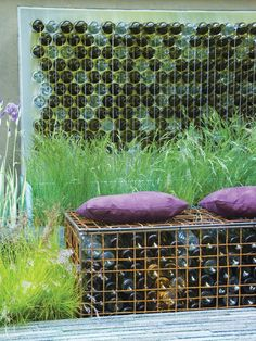 Gabions are usually filled with rocks and used to build retaining walls and to stabilize soil. In this garden, gabions filled with old bottles become a decorative element in the wall and bench.