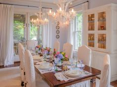 This Hamptons dining room has a large wood dining table, white chairs, am ornate hutch with glass front doors, floor to ceiling curtains and dual hanging chandeliers.