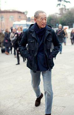 ブラックのM65をダブルブレステッドのジャケット、グレーのパンツを合わせたジャケパンにあわせる高齢白髪のアジア系男性