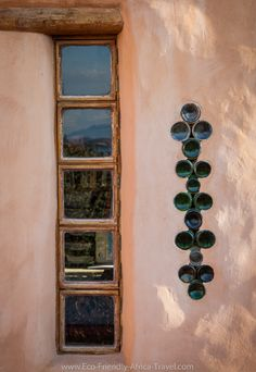 A window in a cob wall alongside a patterned glass bottles.