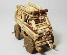 Toy car made from cassava stalks with a stick for pushing it along, attached by a plastic string. (1998.9.4)