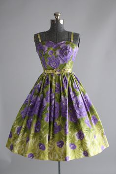RESERVED  This 1950s cotton dress features a gorgeous floral print in shades of purple and green. Spaghetti straps. Full pleated skirt. Metal zipper up back of dress. Includes the original belt and the matching cropped jacket. Very good vintage condition. Please note: there are