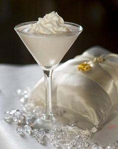 Wedding Cake Martini made with vanilla vodka and coconut rum. Ingredients: 1.5 oz vanilla vodka, 1/2 oz Malibu coconut rum, 1.5 oz pineapple juice, 1 splash grenadine syrup... Blend ingredients together and top with whipped cream. Serve in Martini glass