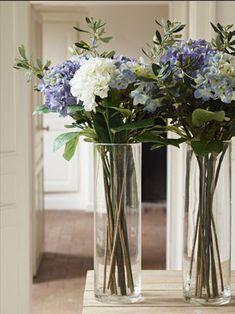 Bonito centro de mesa con hortensias azules, peonias blancas y ramas de olivo.