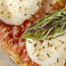 grilled flatbread pizza with roasted garlic, ricotta cheese, fresh tomatoes and basil