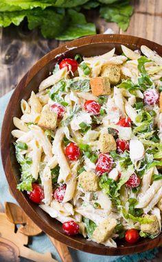 Caesar Salat mit Hühnchen, Zutaten: 1 Tasse Mayonnaise, ⅓ Tasse saure Sahne, 1 große Knoblauchzehe, gepresst, 2 EL Zitronensaft, 2 Anchovis, fein gehackt, 1 TL Worcestershire-Sauce, 1 Pfund Penne Nudeln, gekocht, al dente und mit kaltem Wasser abgespült, 6 große Blätter Römersalat, in dünne Scheiben geschnitten, 1½ Tassen Cherrytomaten, 4 Frühlingszwiebeln, ½ Tasse feiner Parmesan,  ½ TL gemahlener schwarzer Pfeffer, 2x gegrillte Hähnchenbrust, gewürfelt, 1½ Tassen C