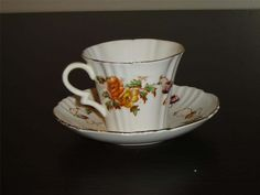 """The design is a vine with purple, orange, and yellow flowers, gold banding on the edges  The cup is 2 9/16"""" (6.5 cm) high x 3 5/16"""" (8.4 cm) at the brim and the saucer is 5 1/2"""" (14 cm) in diameter  The cup in this set is marked 1542, the saucer has no such mark  There is a small (1/8"""") hairline crack at the brim of the cup but otherwise this set is in good condition and doesn't appear to have been used as anything other than a collectible  Made of bone china from England by Royal Albert at…"""