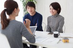 Real estate agent is description to couple about  new house stock photo