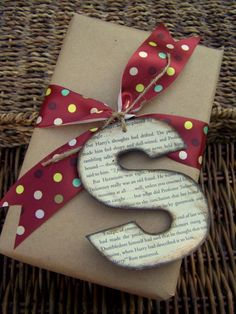 Sinterklaas verpakking. Een mooie strik en een letter, geknipt uit een boek. Maak met een sponsje en inkt de randen van de letter zwart.