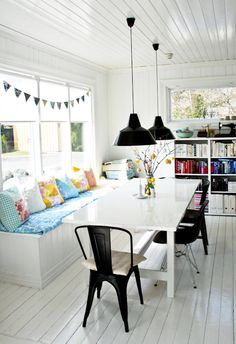 Beautiful boho chic dining area. Love the daybed come seating, the tolix chairs and the kitsch bunting!
