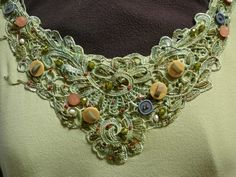 Appliqued lace embellished with buttons, beads, embroidery floss and pearls.