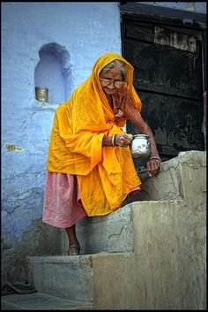 India.  Yellow on light blue - Women of Bundi - Rajasthan. Where is she going? What is she doing? What has she seen in her life? What's her name?