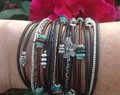 Whatever the occasion, this unique boho leather wrap bracelet is going to wow your colleagues, friends and family. It will look fabulous no matter what youre wearing. For every day, you can wear it with a pair of jeans and white t-shirt and some killer heels but if youre going to a party, team this with a hippy style dress for a super boho statement.  FEATURES: *Four cords of Genuine Dark Brown leather *2 strands mixed turquoise, browns, silver and pearl Miyuki (Japanese Glass) Beads *Silver…
