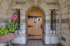 Characteristic of Old World style, the arched front door includes wrought iron details that perfectly complement the historic stone exterior. Old Wood Doors, Wood Front Doors, Arched Front Door, Front Entrances, Castle Pictures, Cottage Door, Wrought Iron Doors, Unique Doors, Expensive Houses
