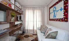 A moradora tem paixão por gatos e o bichano estampa o quadro de Clarys Zanardo Lottito, pendurado sobre o sofá, que tem almofadas trazidas de viagem. Entre a sala e a cozinha, um móvel abriga a bancada de refeições, a TV e o ar-condicionado. Projeto de Cristiane Dilly.