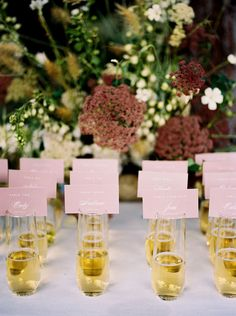 Escort cards attached to glasses of champagne.