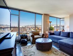 An apartment living room in an eclectic style. It combines a traditional rug with a leather ottoman, blue sectional sofa, and patterned armchair. The furniture ranges in wood grain and shade. The most impressive part of this living room is the cityscape view through the extensive floor-to-ceiling windows.