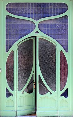 Minimalist Art Nouveau door with green ironwork details. I like how this almost has a Deco/Nouveau style.
