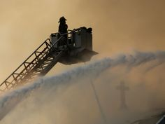 Chicago firefighters work at the scene of an extra-alarm fire at Shrine of Christ the King Church in Chicago. About 150 firefighters responded when flames engulfed the 92-year-old church on Chicago's South Side.  Jose M. Osorio, Chicago Tribune, via AP