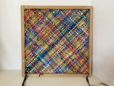 Approximately 11 inches square on the loom. Mixed ribbon yarns. #25.