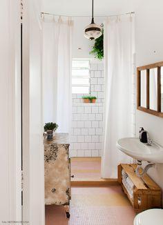 Depois de uma reforma simples, esse banheiro ganhou azulejos brancos aplicados com rejunte preto e um piso de pastilhas na cor rosa e amarelo.
