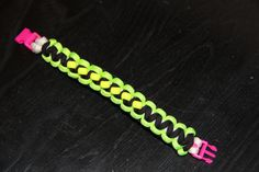 Paracord Survival Bracelet with Clip White Pink by CordNinja. Paracord Survival Bracelet with Clip - White, Pink, Black, Green, and Yellow.
