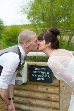 "The bride & groom stop for a kiss before entering the ""no petting"" area at Jimmy's Farm, Suffolk. www.headoverheelsphotography.co.uk"