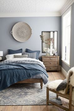 Modern bedroom design featuring a blue, gray, white and wood tone color scheme, a large woven basket as wall decor over the bed, layers of blue, gray, and white bedding, a large antiqued mirror over a wood bedside table, and a sheepskin throw on a wood chair - Home Decor & Decorating Ideas - mydomaine.com