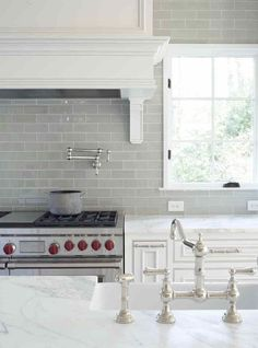 gray glass kitchen backsplash with carrera marble counters in a pretty traditional white kitchen. Nickel faucet and wolf range