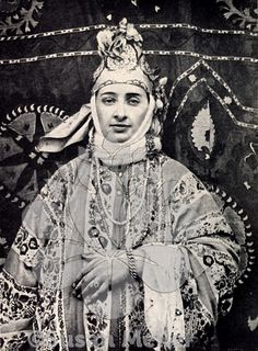 """BELLE of OLD TASHKENT in WEDDING COSTUME"", Tashkent, Uzbekistan. 1906.  The woman wears a dress made from Russian printed-cotton. SUZANI background"