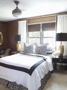 This window treatment idea could work for my bed under the window. Extending the side panels past the window frame would make the window look larger and the roman shades are good for light control.