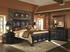 This Master bedroom has a partial accent wall that is grey stone framing the head board of the bed.
