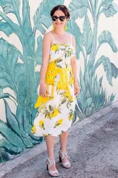 Jennifer Lake Style Charade in a lemon print tie front dress, lemon print cardigan, yellow stripe clutch, and yellow tassel earrings at a leaf print wall Outfit Trends, Trend Outfits, Summer Outfits, Modest Fashion, High Fashion, Fashion Outfits, Fashion Tips, Dolce & Gabbana, Yellow Tassel Earrings