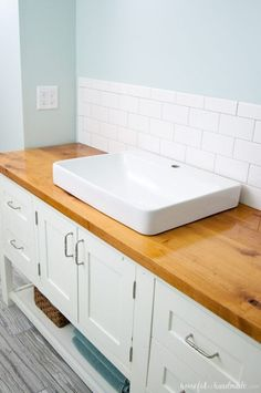 I absolutely love the look of this bathroom vanity! Add some rustic warmth to your farmhouse bathroom by adding a waterproof wood vanity top. Learn how to build & protect a wood vanity top for your next DIY renovation. Wooden Bathroom Vanity, Wood Vanity, Master Bathroom, Bathroom Sinks, Bathroom Cabinets, 1920s Bathroom, Garage Bathroom, Bathroom Showers, Downstairs Bathroom