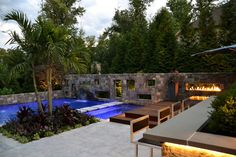 Escape from the chaos and browse through this gorgeous backyard design by Scenic Landscaping. A custom, tropical pool is the star of the design, with its see-through stone wall, floating marble stepping stones and fireplace inlay. Other features include a raised patio and a glorious outdoor kitchen.