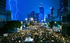 Lightning strikes as protesters gather outside government headquarters. Many began singing in the rain. Photo: Bloomberg