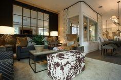 salon élégant aménagé avec un canapé gris, fauteuils et tabouret imprimé vache, lampes de table élégantes et tapis gris clair