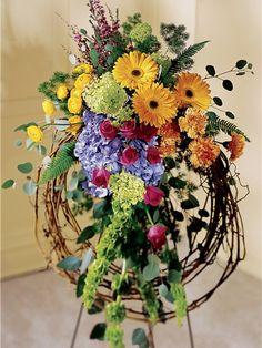 A colorful funeral arrangement including blue hydrangea on a grapevine wreath