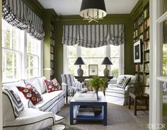 In this Nashville home, the sunroom's sofa and armchairs are upholstered in a canvas duck, and the Regency library chair is covered in the same Quadrille cotton stripe as the Roman shades. The walls are painted in Duron Paints & Wallcoverings' Palmetto.