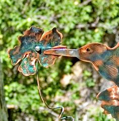 Hummingbird metal yard art copper garden plant stake plant by Garden Copper Art is created with artistic twisted solid copper wire wrapping, an artist touch of artistic free flowing melted soldered applied to beak and wings. Hummingbird beak is attached to flower for sturdy life of the stake, in windy conditions. This unique one of a kind stake is accented with a heart and hammered flower. This adorable nature bird will make a lovely gift for all nature lovers. Available now for purchase…