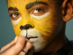 To give your child a ferocious lion's face for Halloween, simply paint a basic orange and yellow face. Darken and thicken eyebrows with black or dark brown paint or shadow. Dip a thin paintbrush into water then coat with a generous amount of black paint. Paint nose black, focusing on the bottom tip. Next, paint a line connecting the bottom of the nose to the top lip, creating a cat-like mouth separation.