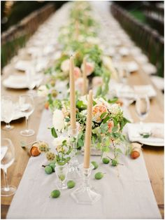 Warm neutral tablescape of green and peach, scattered fruits, neutral taper candles, cut glass