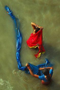 India - Women washing saris in the river.