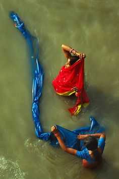 India - Women washing saris in the river.
